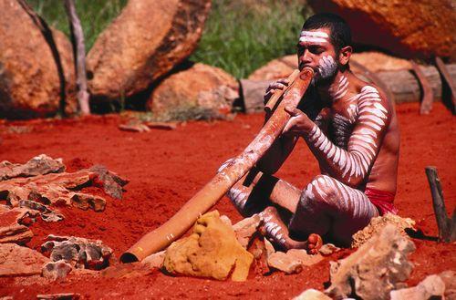 Aborigen tocando (o al menos intentándolo) un didgeridoo.