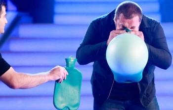 L'uomo che gonfia le borse dell'acqua calda con il naso