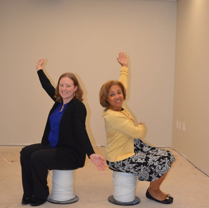 Picture of Wendy and Gina sitting in the empty new office on two spools of wire waiting for the funds from our Dig In for New Digs campaign.
