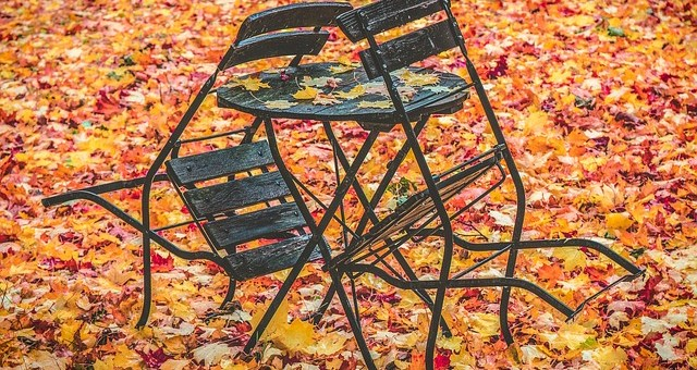 two cafe chairs tipped against a small table. Table and ground are covered with fall leaves mostly red in variety