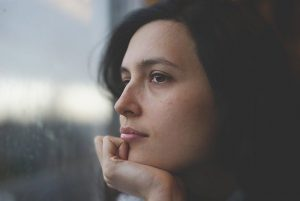 woman looking thoughtfully out a window