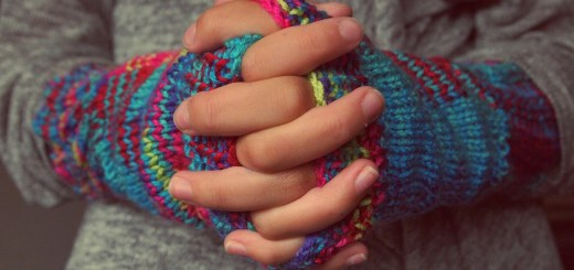 hands folded in front with fingers intertwined, knit handwarmers on the hands