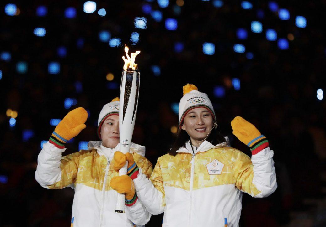 Deux hockeyeuses, une de la Corée du Nord et l'autre de la Corée du Sud, ont porté la flamme olympique ensemble. - (AP Photo/Petr David Josek)