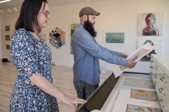 Christine Comeau et Mario LeBlanc viennent d'ouvrir la galerie Murmur sur la rue St-George à Moncton. On les voit en train de regarder certaines oeuvres de leur inventaire. - Acadie Nouvelle: Sylvie Mousseau