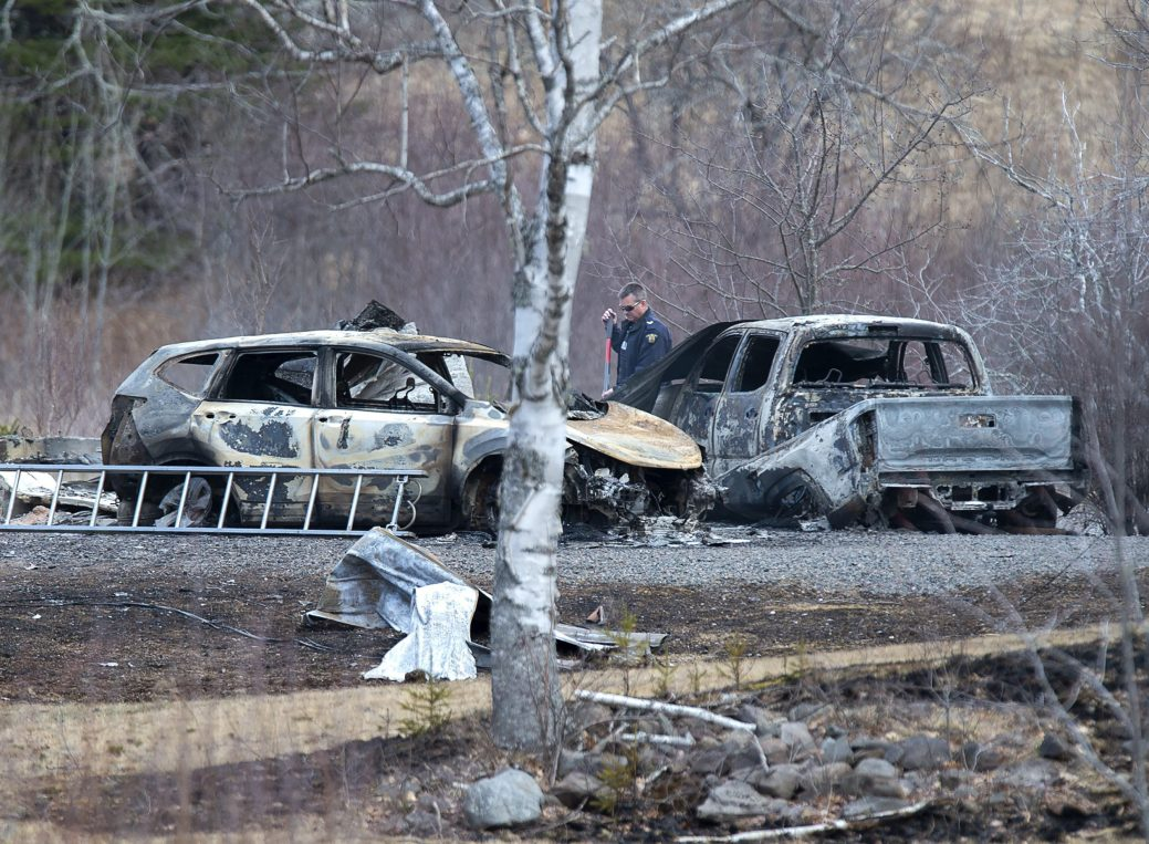 Un enquêteur de la GRC inspecte des véhicules détruits par le feu à la résidence d'Alanna Jenkins et de Sean McLean, tous deux agents correctionnels, à Wentworth Center, en Nouvelle-Écosse. - Presse Canadienne