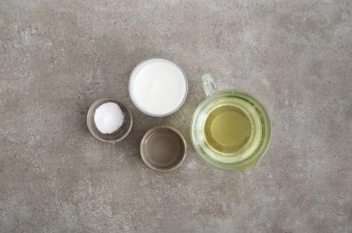 Ingredientes para fazer maionese vegana vistos de cima. Sal, leite, óleo e suco de limão.