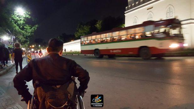 ภาพซาบะนั่งรถเข็นใส่ถุงมือ แต่งชุดทำงานสีดำ ช่วงมืดค่ำ กำลังเข็นรถไปตามริมถนนสวนกับรถเมล์ที่กำลังวิ่งมา มอเตอร์ไซด์และคนเดินกันอย่างพลุกพล่าน