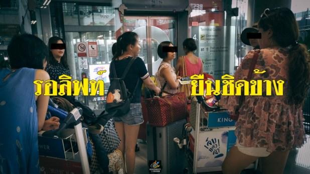 ภาพนักท่องเที่ยว 8 คนพร้อมกระเป๋าเดินทางยืนรอ ออกันอยู่หน้าลิฟท์ภายในสนามบินสุวรรณภูมิ มีตัวหนังสือ caption สีเหลืองเขียนแปะไว้ 'รอลิฟท์ ยืนชิดข้าง'