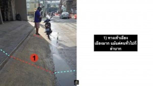 ภาพ คนขับมอเตอร์ไซด์ จอดและยืนอยู่ข้างๆ ยืนอยู่บนทางเท้าที่มีความเอียงมาก