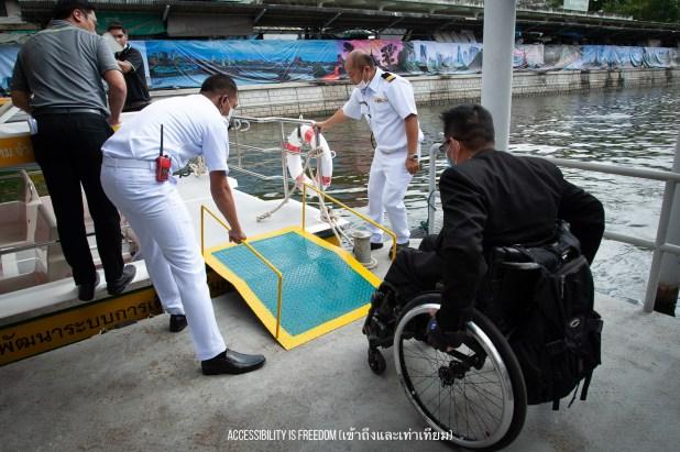 ภาพ พี่ซาบะกำลังเข็นรถขึ้นทางลาด ขึ้นเรือ มี จนท ใส่ชุดขาวกำลังคอยให้บริการ