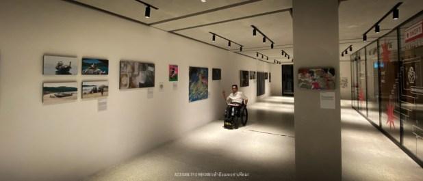 ภาพ พี่ซาบะกำลังดูงานศิลปที่จัดแสดงตามผนัง