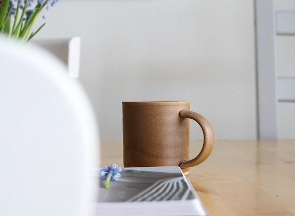 Koffie drinken uit een donkerbruine mok aan een houten tafel - via Accessorize your Home