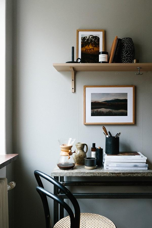Werkkamer met licht muur voorzien van planken met verzameling keramiek en fotokunst van Kolla - via Accessorize your Home