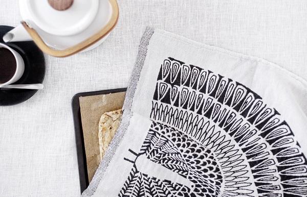 Flat lay van ontbijt tafel met brood, theepot en theedoek met print in zwart - via Accessorize your Home