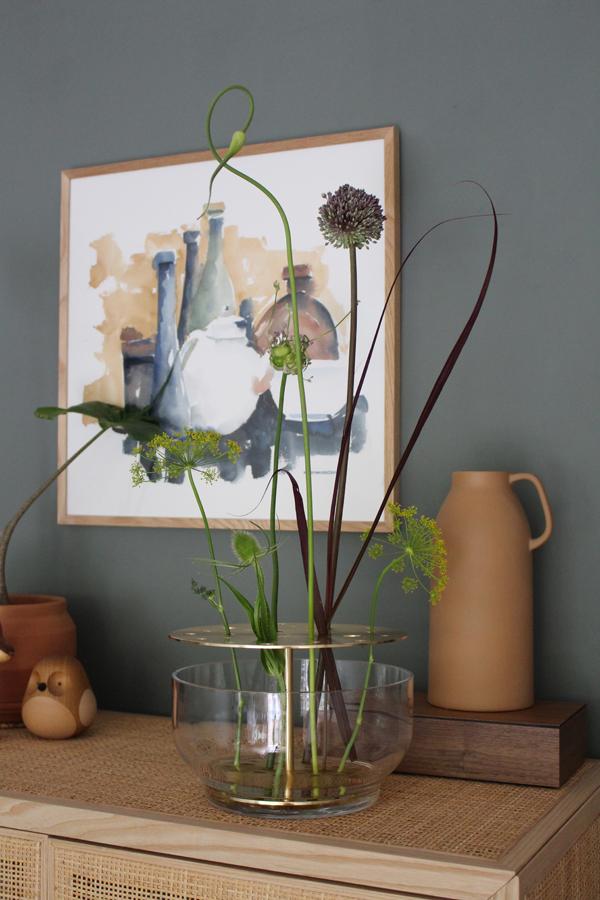 Ikebana vaas van Jaime Hayon op een rotan kast tegen een donkergroene muur - via Accessorize your Home