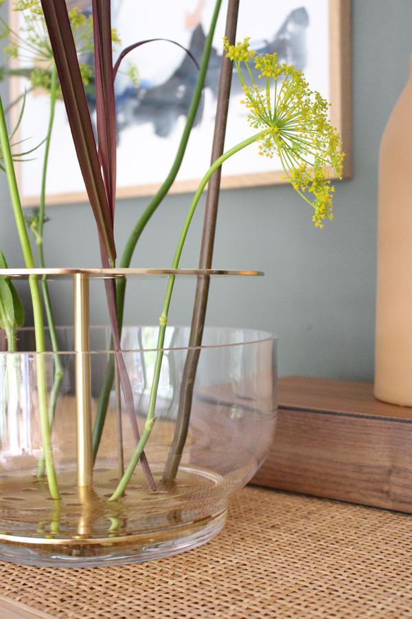 Detailfoto van de messing schijven van de Ikebana vaas met dille op een rotan kast tegen een donkergroene muur - via Accessorize your Home