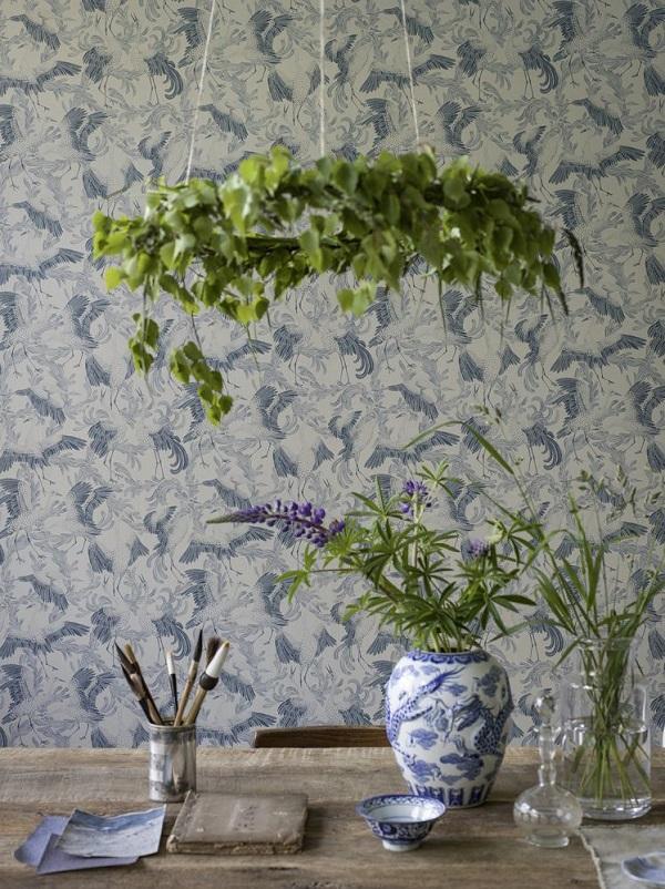 Behang met dansende kraanvogels in blauw met houten tafel en vaas met bloemen - via Accessorize your Home