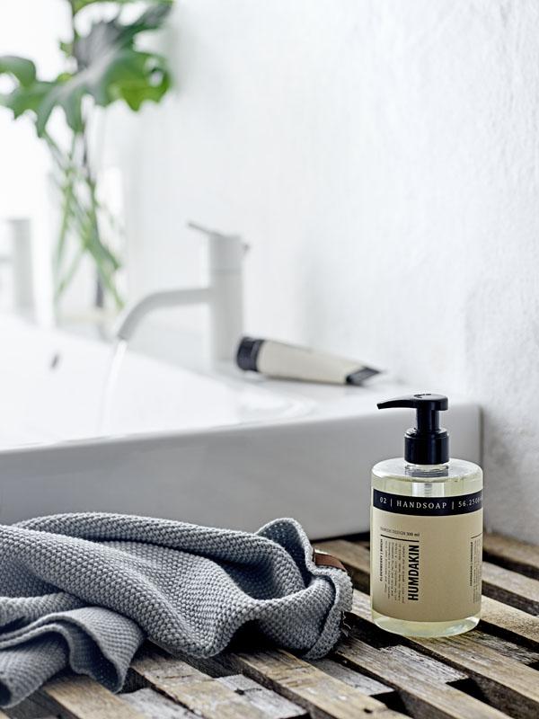 Handlotion in mooie tube met grijze katoenen handdoek bij witte wastafel - via Accessorize your Home