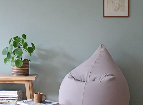 Lichtgrijze zitzak van Terapy tegen groene muur met Pilea plant - via Accessorize your Home