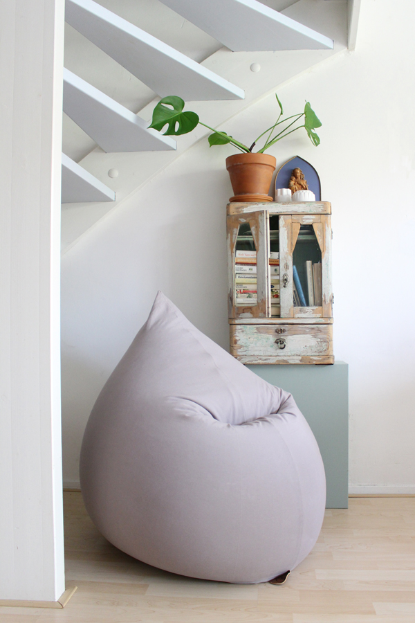 Lichgrijze zitzak onder de trap met vintage kastje en Monstera plant - via Accessorize your Home