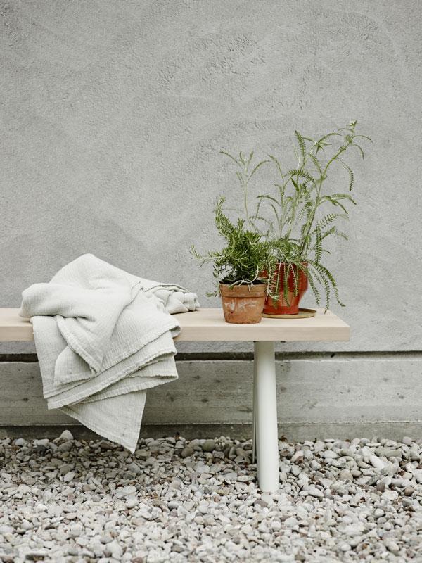Houten bankje met witte poten op terras met terra cotta potten met planten en een wit plaid - via Accessorize your Home