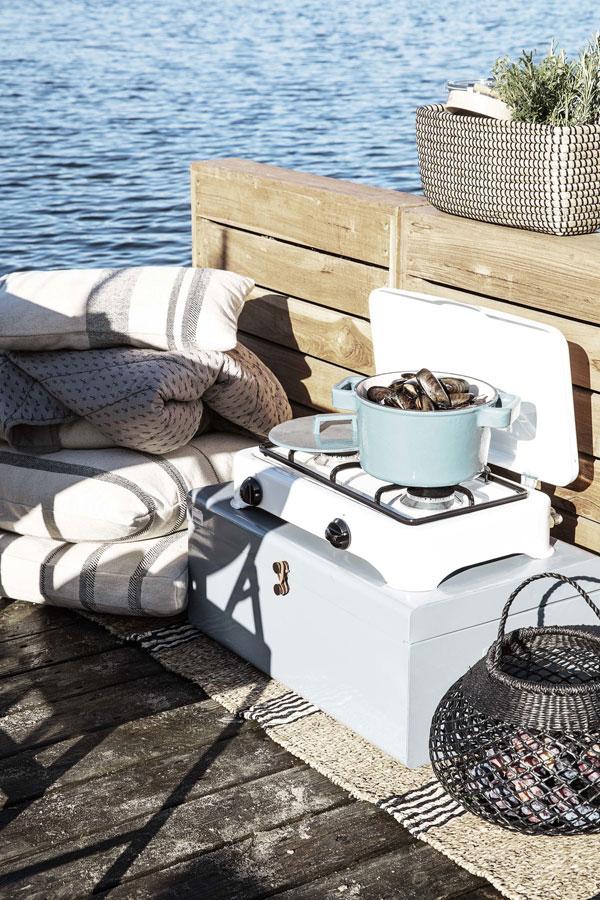 Buiten koken op een zonovergoten houten ponton met een rechaud en blauwe gietijzeren pan van House Doctor gevuld met mosselen.