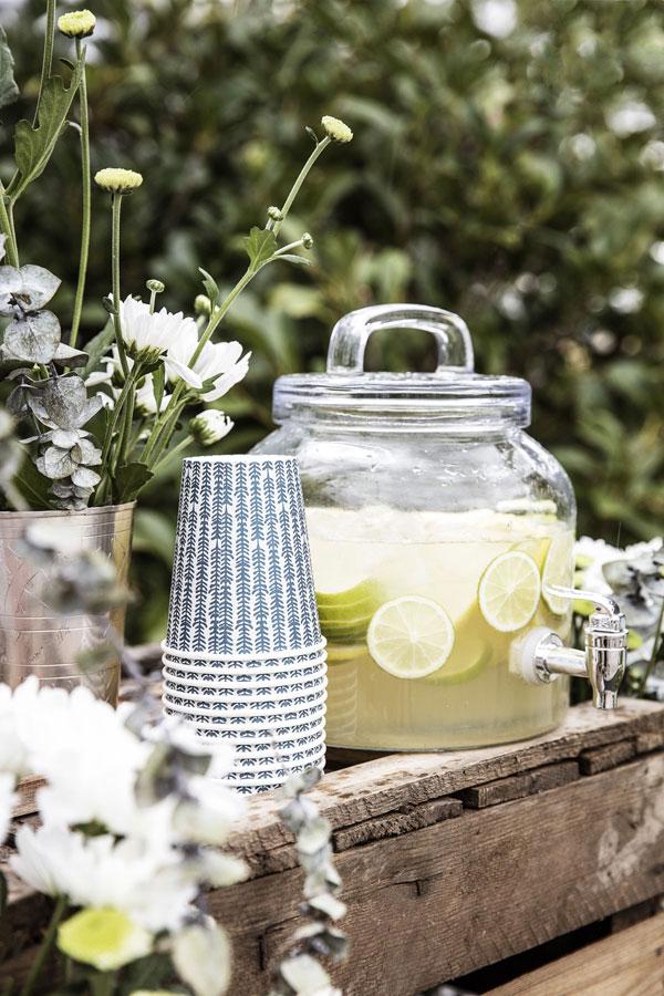 Feestje in de tuin met papieren bekers met print in blauw en glazen sapkan met kraan gevuld met verse citroenlimonade.