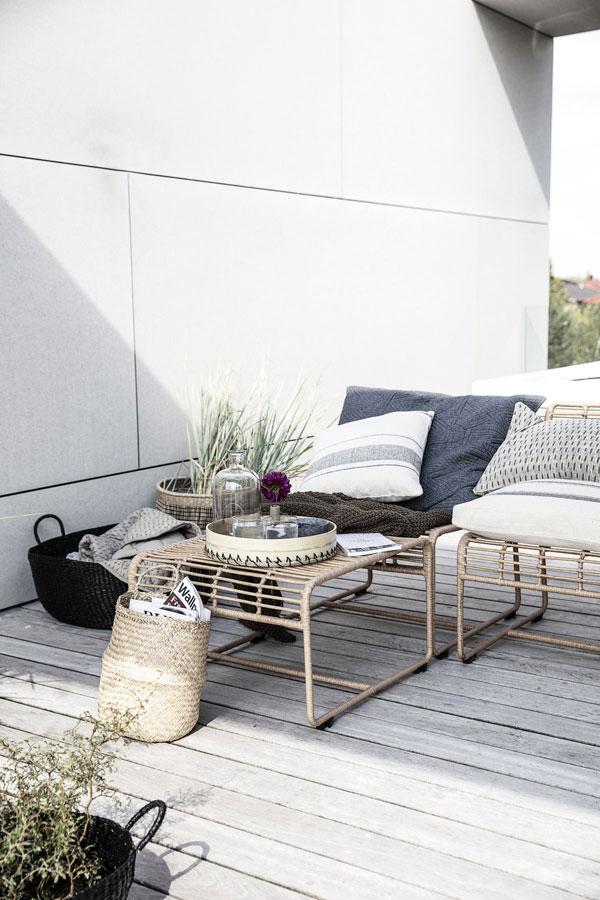 Sfeerbeeld van terras met houten dek en naturel loungestoelen met katoenen kussens en manden gevuld met boeken en planten.