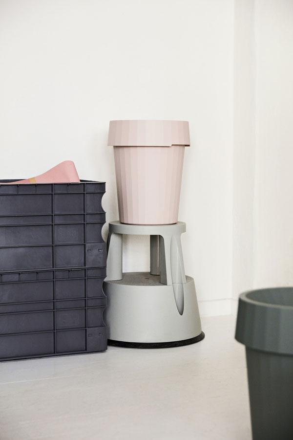 Vergrijsd roze prullenbak naast stapel zwarte kratten tegen witte muur - via Accessorize your Home