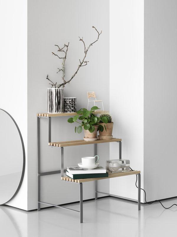 Hoekige plantenstandaard van metaal met houten treden waarop planten en stapeltjes boeken liggen - via Accessorize your Home