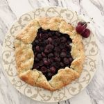 A rustic cherry galette on a decorative pie serving plate with three fresh cherries on the side