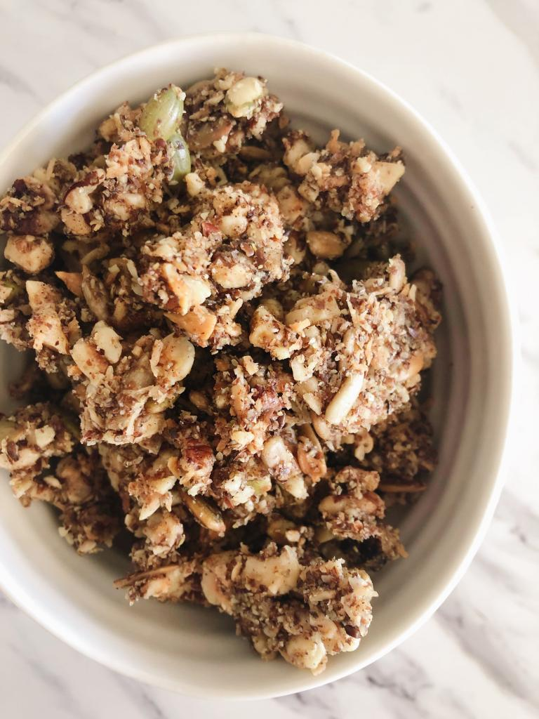 A small white bowl filled with nutty granola clusters on a white countertop
