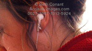 Stock Photography of Young Woman With Earphones in Her Ears