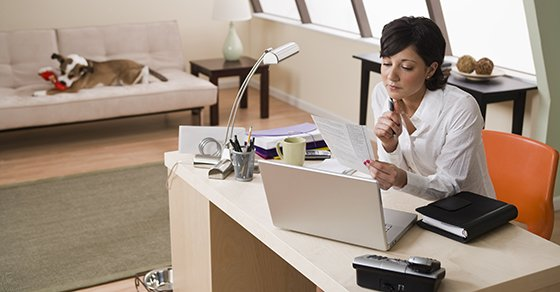 Woman sitting by her laptop in her home office