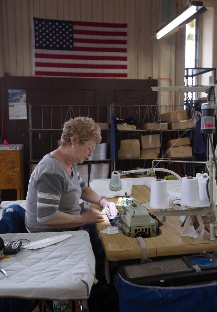 Woman at sewing machine with American Flag