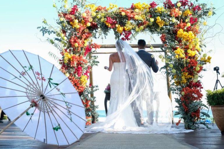 Arco de flores em tons quentes para casamento em buzios