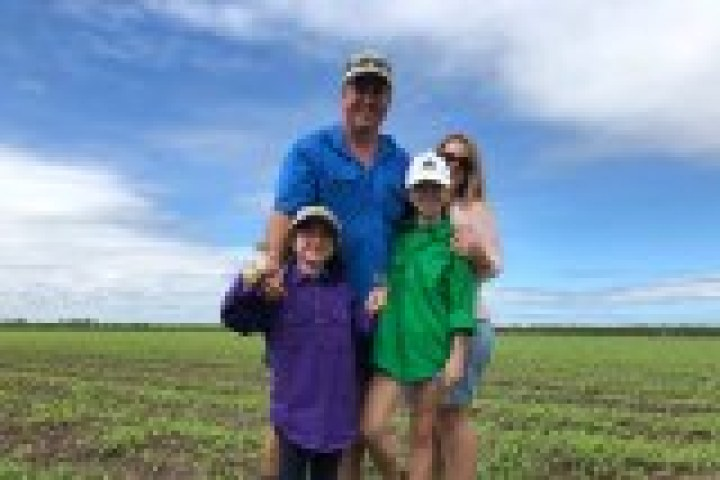 man with daughters in bean paddock