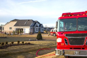 photo of fire engines and fire fighters standing together at scene of house fire that was later rebuilt by Acheson Builders