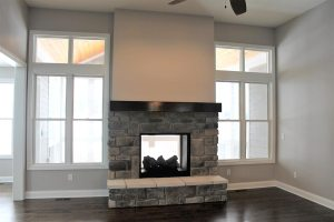 photo of fireplace open to adjoining sun room showing glassed view through fireplace and large windows on either side