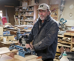 photo of Tim using a router in the shop at Acheson Builders