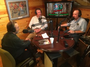 3 men at a table with headphones and microphones, recording an episode of Tennessee WildCast
