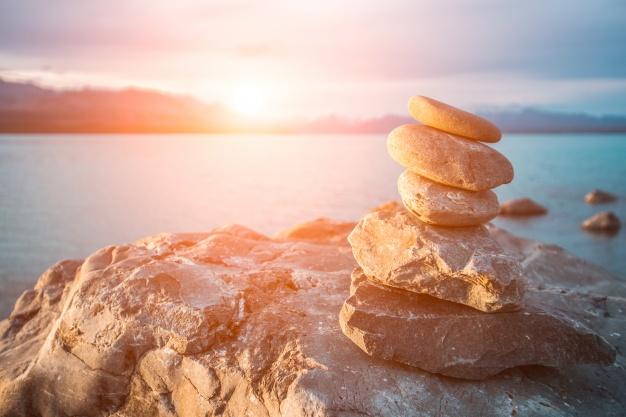 pierres-empilees-dans-mer-au-coucher-du-soleil_1088-589