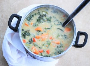 A pot of Creamy (Dairy-Free) Sweet Potato, Kale, and Cannellini Bean Soup with a ladle in it