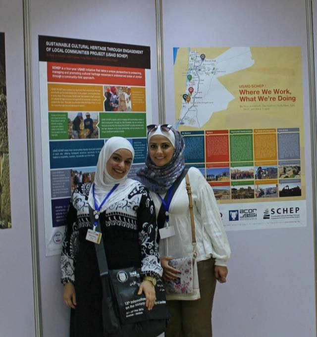 USAID SCHEP interns Haneen Khalifa (left) and Rawan Apsch at the ICHAJ poster session, standing in front of the posters that presented USAID SCHEP's methodology and on-site work. Photo by Sofia Smith.