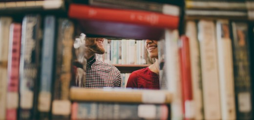 This image shows two people standing behind a stack of library books on a shelf. The books are arranged in an open cube so that their faces are visible through the gap