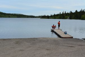 two people in lifejackets on floating dock next to boat launch