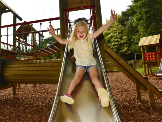 Girl on play tower slide