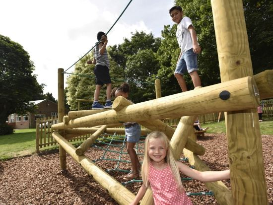 Children playing on one of our popular Forest Stack climbing frames