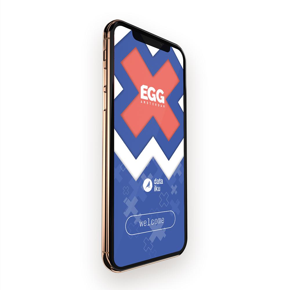 Dit is een afbeelding van een smartphone voor EGG Amsterdam 2019 #EGGAMS2019 dat in Pakhuis de Zwijger werd gehouden. Op de smartphone zien we de huisstijl van EGG Amsterdam, bestaande uit drie Amsterdamse kruizen en blauwe of roze logo van EGG Amsterdam. Daaronder het logo in wit van Dataiku. De stijl van EGG Amsterdam is volledig ontwikkeld door Activates merkversterkend reclamebureau uit Sassenheim in opdracht van Dataiku en Karin Heppener van Heppener makes it happen!