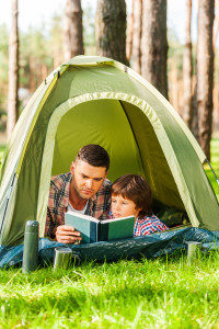 Spending good time outdoors. Father and son reading book while lying in tent together